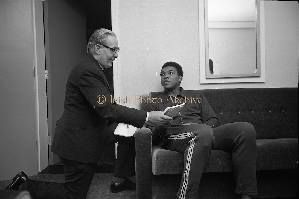 Muhammad Ali In Ireland..1972..14.07.1972..07.14.1972..14th July 1972..A short film on Muhammad Ali in Ireland has been made for showing in the USA before his bout with Al 'Blue'Lewis.The film sponsored by Bord Failte is produced and directed by Mr Louis Marcus.Commentary is provided by Muhammad Ali himself.The project was discussed at Oppermans Country Club Hotel,Kilternan,Co Dublin,where the Ali camp was based...Pictured adding a few comments to the script is Muhammad Ali accompanied by Mr Tom Sheehy,Bord Failte.
