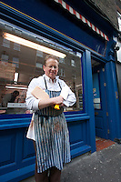 Portrait of a happy senior butcher standing outside shop with cleaver