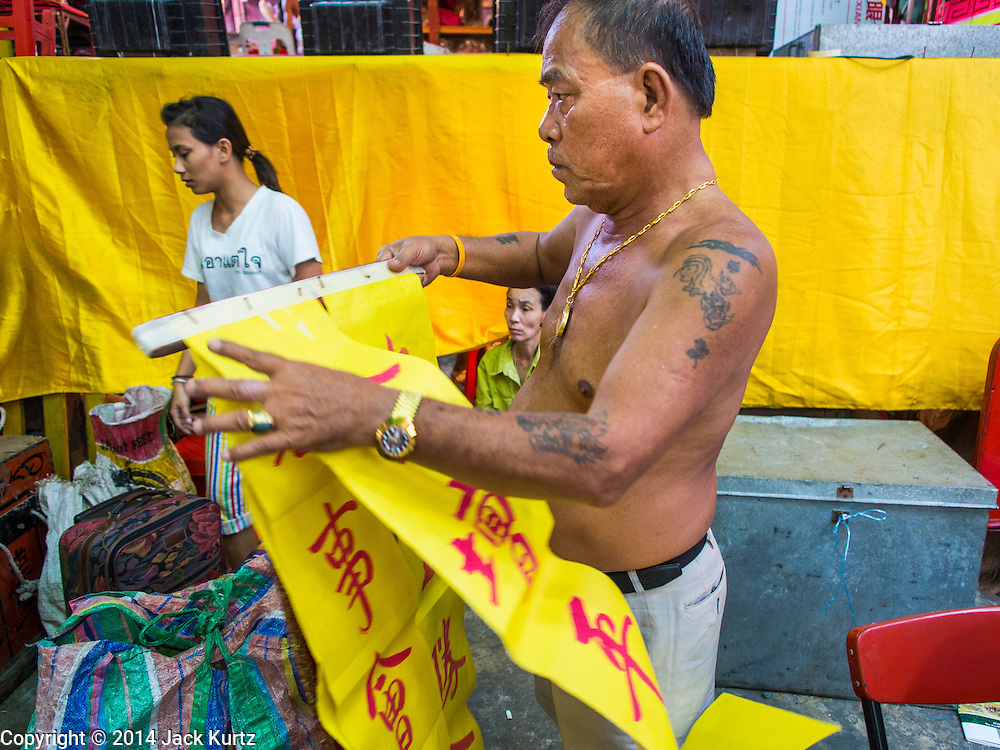 23 SEPTEMBER 2014 - BANGKOK, THAILAND: A man carries banners written in Chinese announcing a Chinese opera performing at the Chit Sia Ma Chinese shrine for the vegetarian festival in Bangkok. The Vegetarian Festival is celebrated throughout Thailand. It is the Thai version of the The Nine Emperor Gods Festival, a nine-day Taoist celebration beginning on the eve of 9th lunar month of the Chinese calendar. During a period of nine days, those who are participating in the festival dress all in white and abstain from eating meat, poultry, seafood, and dairy products. Vendors and proprietors of restaurants indicate that vegetarian food is for sale by putting a yellow flag out with Thai characters for meatless written on it in red.    PHOTO BY JACK KURTZ