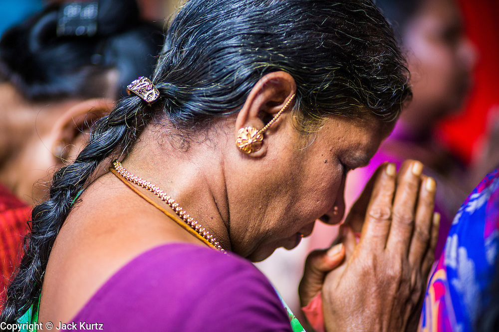 07 JANUARY 2014 - SINGAPORE:   A woman prays during afternoon pooja in Sri Veeramakaliamman Temple, a Hindu temple located in Little India in the southern part of Singapore. The Sri Veeramakaliamman Temple is dedicated to the Hindu goddess Kali, fierce embodiment of Shakti and the god Shiva's wife, Parvati. Kali has always been popular in Bengal, the birthplace of the labourers who built this temple in 1881. Images of Kali within the temple show her wearing a garland of skulls and ripping out the insides of her victims, and Kali sharing more peaceful family moments with her sons Ganesha and Murugan. The building is constructed in the style of South Indian Tamil temples common in Tamil Nadu as opposed to the style of Northeastern Indian Kali temples in Bengal. PHOTO BY JACK KURTZ