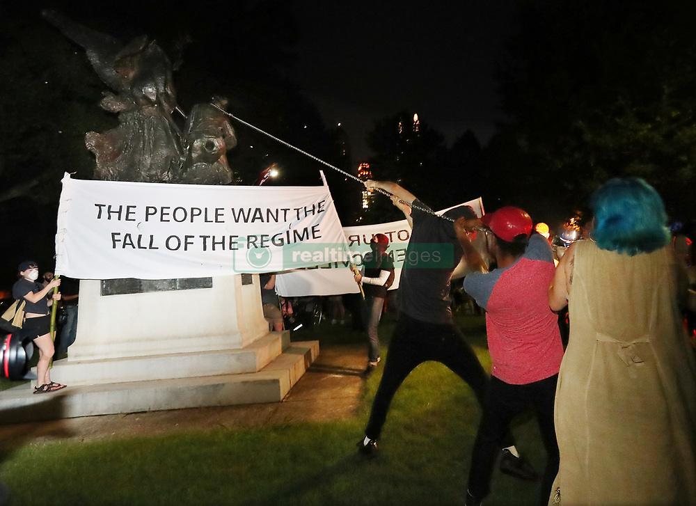 After marching from Woodruff Park to Piedmont Park during a anti white nationalism memorial and march in response to violence in Virginia, protesters try to topple a Confederate monument with a chain on Sunday, Aug. 13, 2017, in Atlanta. The peace monument at the 14th Street entrance depicts a angel of peace stilling the hand of a Confederate soldier about to fire his rifle. Photo by Curtis Compton/Atlanta Journal-Constitution/TNS/ABACAPRESS.COM