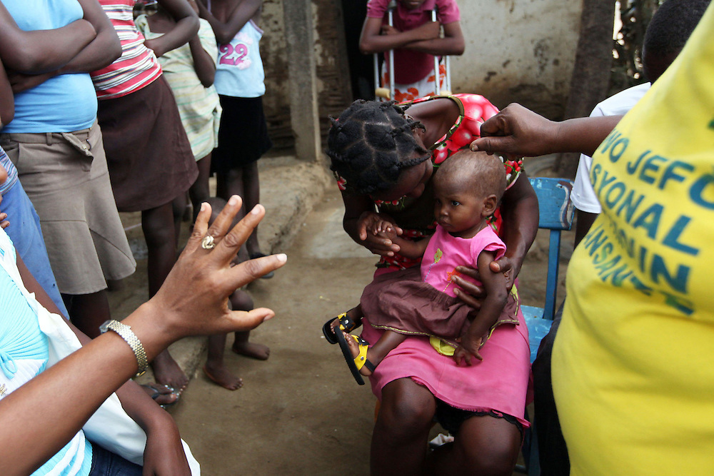 A volunteer waves her hand in front of a child's face to make sure the child responds accordingly during a home visit in Trou-du-Nord, Haiti.  Haiti's Pastoral da Crianca struggles to keep volunteers, as many want to paid for their work.  The Pastoral da Crianca draws volunteers from the communities  they serve, so that familiar faces are doing home visits, and the volunteers in turn become pillars of their communities.
