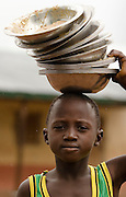 A boy carries dirty metal bowls used for lunch on his head at the Nyologu Primary School in the village of Nyologu, northern Ghana, on Wednesday June 6, 2007. ..
