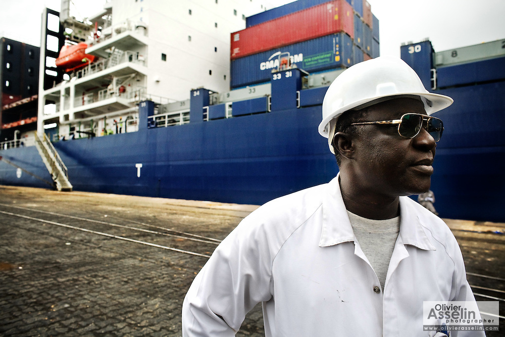 A worker stands by a large cargo boat at the sea port in Lome, Togo on Friday October 3, 2008.