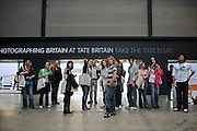 A Raw Canvass tour guide shows a group around the Turbine Hall at Tate Modern.