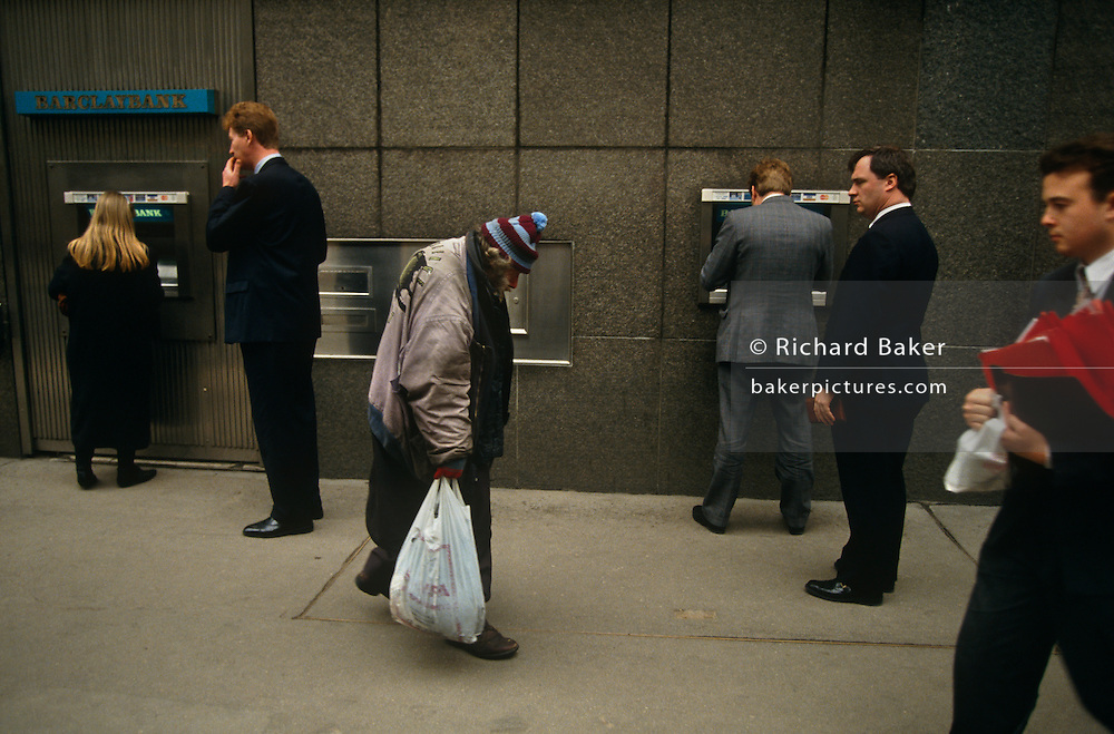 An elderly homeless man walks slowly past a Barclays Bank cash dispenser at which business people are either queueing or typing in their PIN numbers from cash accounts, or simply passing-by. One middle-aged gent stands eyeing the poor man suspiciously while other men of wealth, prospects and prosperity are tall and stand erect in smart suits and polished shoes, the homeless man is hunched and dishevelled, carrying a supermarket bag - perhaps containing all of his worldly goods. It is a tragic scene of extremes between the haves and the have-nots; the rich and poor; between people with hope and those in despair. This is the City of London, near Fenchurch Street Station where the UK's insurance companies are based and it is impossible to know if any of these men in smart clothes are the same age as the poor man.