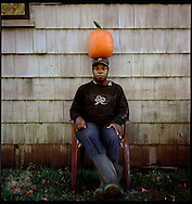 Migrant farm worker Gladstone Watkins balances a pumpkin on his head outside his home at March farm in Bethlehem, CT. Watkins, from Jamaica, says he has picked fruit all over the east coast and spent 13 years picking tobacco. (Photo by Robert Falcetti)