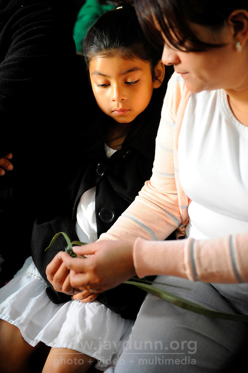 A mother shows her daughter how to twist a palm frond into an offering at the 9:00 AM Palm Sunday Mass at El Cristo Rey church in Salinas.