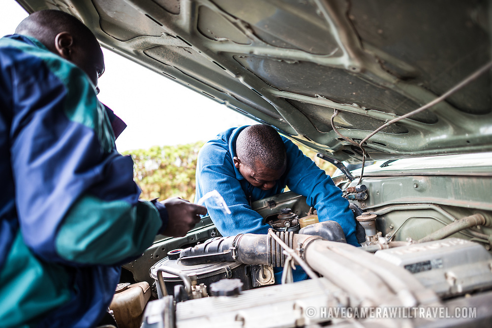 Repairing a broken engine of a Toyota Landcruiser at Londorossi Gate, one of the National Park ranger gates to Kilimanjaro National Park, and the gate one must check in to when climbing the Lemosho Route of Mount Kilimanjaro.