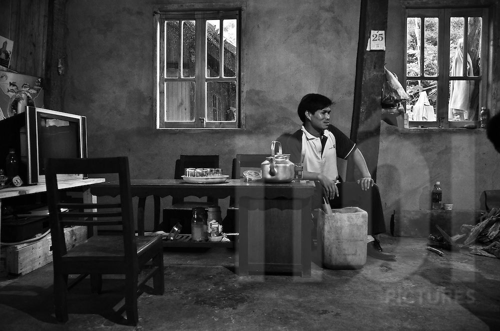 A guest is seated in the living-room part of the room where ther is a pipe, the teapot and tea set, traditional vietnamese furnitures and a tv screen. He is watching the family preparing dinner, in  Sapa surroundings, Lao Cai province, North Vietnam.