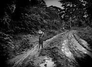 Young boy finds it difficult to return to his village with harvest from his family's farm plot, his father trailing behind, along a muddy, road deeply rutted by logging trucks because of selective logging further in the rainforest.  East of Nguti, Cameroon.  Logging trucks dig up roads local people have used for generations making it difficult to simply walk along them, let alone navigate them with a vehicle of any kind.   <br /> Herakles Farms' concession would be very close to this location, though Herakles would clear-cut the forest to convert it to an oil palm plantation, completely decimating the environment and dislocating farmers.