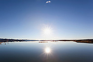 Sunset at the El-Mansour Eddabbi dam with clear blue sky and water reflection, Ouarzazate, Morocco.
