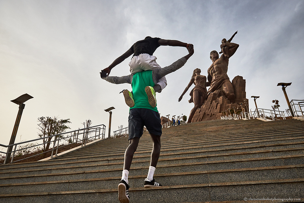 "Kherou Ngor trains on the stair of the ""monument of the African Renaissance"", with a chummy Wrestler"