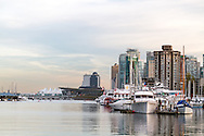 View of Coal Harbour yachts, the Vancouver Trade and Convention Center, Canada Place, and the Pan Pacific Hotel.  Photographed from the Stanley Park seawall along the western end of Coal Harbour in Vancouver, British Columbia, Canada