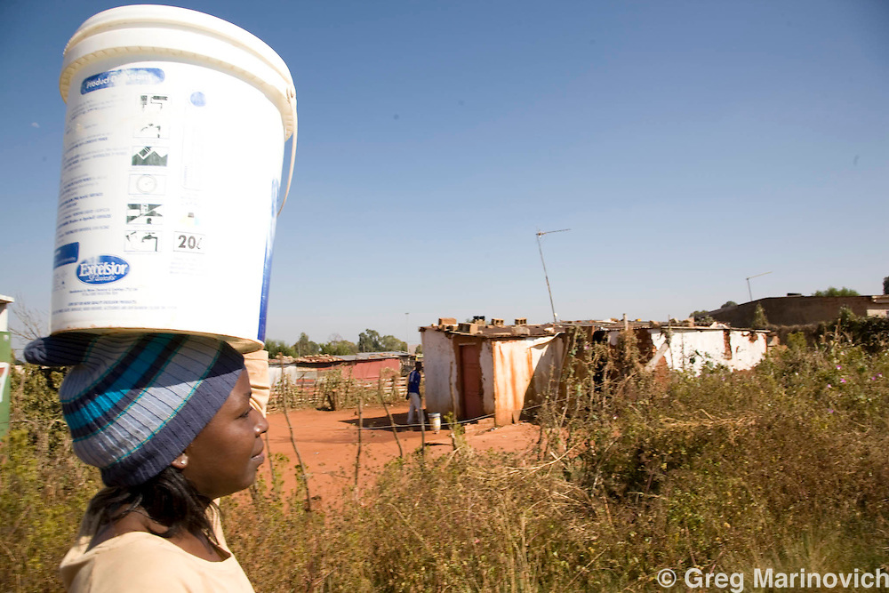 Hospital Hill informal settlement, South Africa April 15, 2009. A 24 year old woman carries the last of several buckets of water to her home where she has no water or electricity, in background a grader levels ground to build houses for the shackdwellers Photo Greg Marinovich