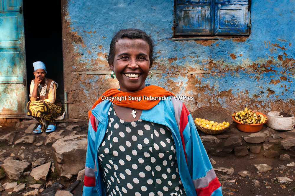 Woman outside of one of the oldest houses in the city of Gondar, Ethiopia. Gondar Imperial city filled with castles of the ancient emperors, also in a modern city. Gondar founded by the emperor Alam Sagad or Fasilidas in the year 1635 and was the last bastion of the Italian occupation, here they retired when the British occupied Addis Ababa. It is surrounded by mountains and from one of them there are spectacular views of the city. We have several streets in the center and we take you with cardamom that is very rich. It is a spectacle to sit in some of their cafes and watch life pass before you.