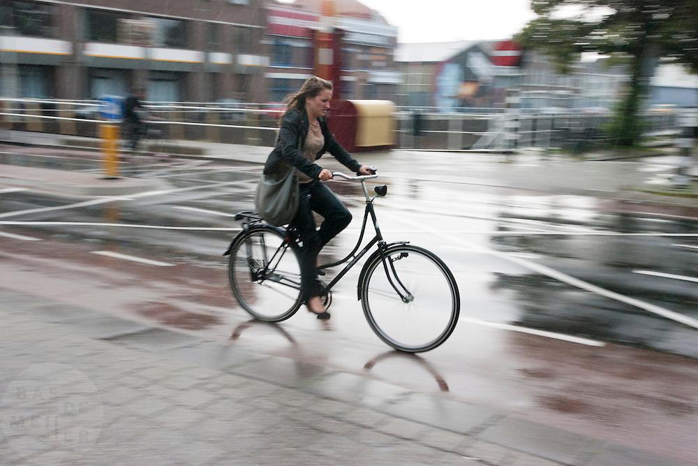 Fietsers rijden door de stromende regen door Utrecht.<br /> <br /> Cyclist in the pouring rain in Utrecht.