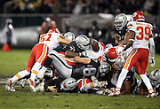 Oakland Raiders quarterback Derek Carr (4) lies at the bottom of a pile after running the ball for a fourth quarter first down on a third down play during the NFL week 12 regular season football game against the Kansas City Chiefs on Thursday, Nov. 20, 2014 in Oakland, Calif. The Raiders won their first game of the season 24-20. ©Paul Anthony Spinelli
