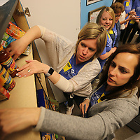 Emily Jarrett, left, and Mika Brown organize the shelves after they helped stock the food pantry at Tupelo High School Monday morning.