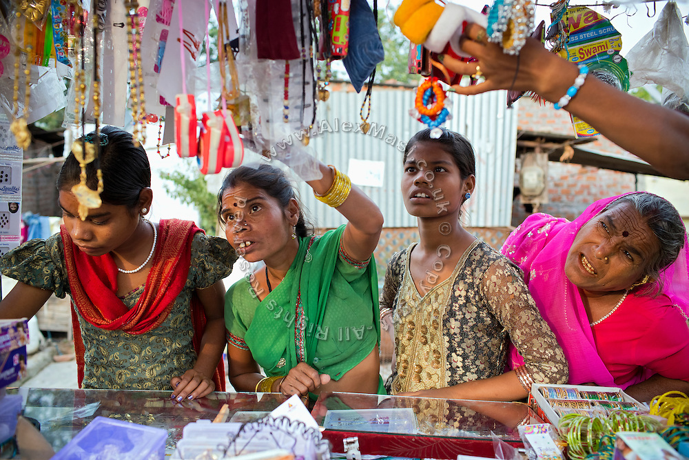 (left to right) Poonam's sister Jyoti, 13, their mother Sanjita, 41, Poonam, 12, and their aunt - visiting today - are checking accessories on sale from a wheeled cart passing in front of the family's newly built home in Oriya Basti, one of the water-affected colonies of Bhopal, Madhya Pradesh, India, near the abandoned Union Carbide (now DOW Chemical) industrial complex.