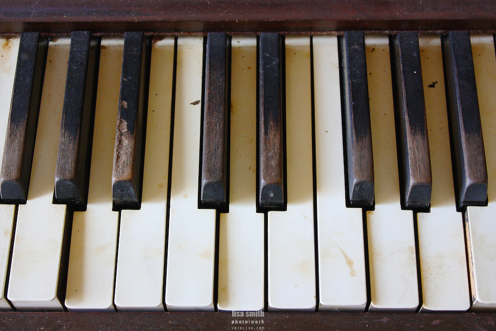 Worn piano keys that have been played for many services, weddings and funerals in a tiny, historical one-room church in rural Texas.