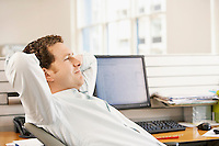 Relaxed mid adult businessman reclining on office chair