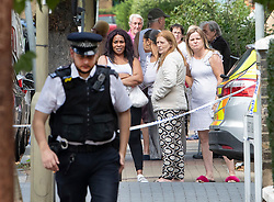 © Licensed to London News Pictures. 15/08/2018. London, UK. Local residents look on as police enter a house where a woman has been stabbed to death in Battersea, South London. A 40 year old male was arrested at the scene on suspicion of murder. Photo credit: Peter Macdiarmid/LNP