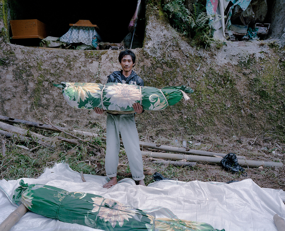 A family member poses for a portrait after adding a new layer of fabric to wrap the remains of a relative in Barrupu.  In this district of Toraja, the body is not buried but placed in a hole carved into a cliff. <br />