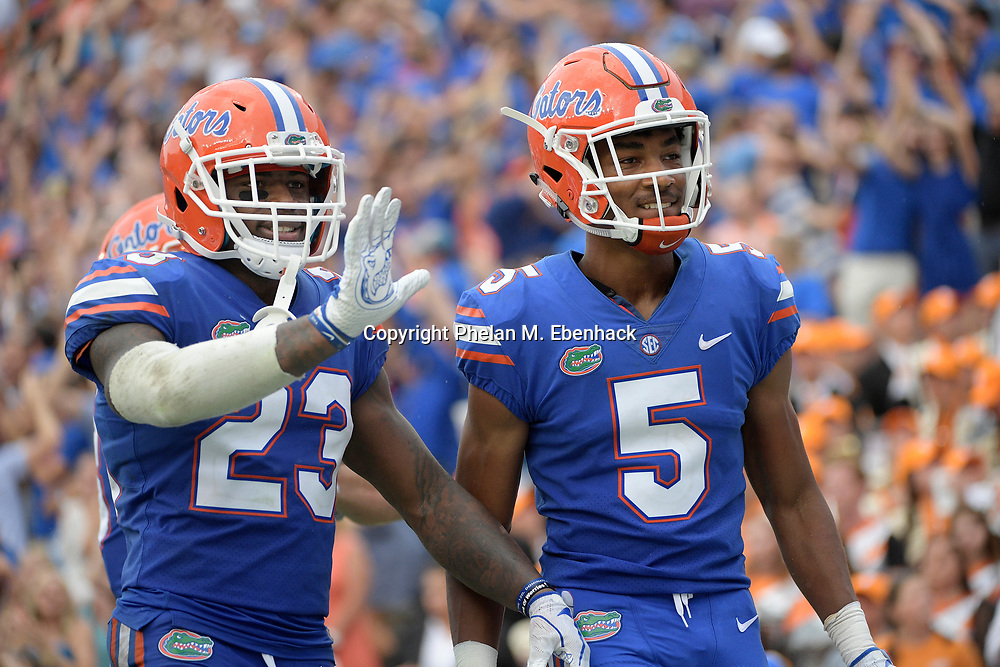 Florida cornerback CJ Henderson (5) and defensive back Chauncey Gardner Jr. (23) celebrate after Henderson returned an interception for a touchdown during the second half of an NCAA college football game against Tennessee Saturday, Sept. 16, 2017, in Gainesville, Fla. Florida won 26-20. (Photo by Phelan M. Ebenhack)