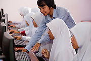 "Sept. 29, 2009 -- SAI BURI, THAILAND: A girl in a computer class at the Darunsat Wittya Islamic School in Sai Buri, Thailand. The school is the largest Muslim high school in Pattani province. Although it is a private school, the Thai government pays students' tuition to attend the school. The curriculum combines Thai official curriculum with Islamic curriculum. Many of the students go on to college level education in Egypt and Saudi Arabia. The Thai government views Islamic high schools with suspicion, fearing they radicalize students. Thailand's three southern most provinces; Yala, Pattani and Narathiwat are often called ""restive"" and a decades long Muslim insurgency has gained traction recently. Nearly 4,000 people have been killed since 2004. The three southern provinces are under emergency control and there are more than 60,000 Thai military, police and paramilitary militia forces trying to keep the peace battling insurgents who favor car bombs and assassination.   Photo by Jack Kurtz"