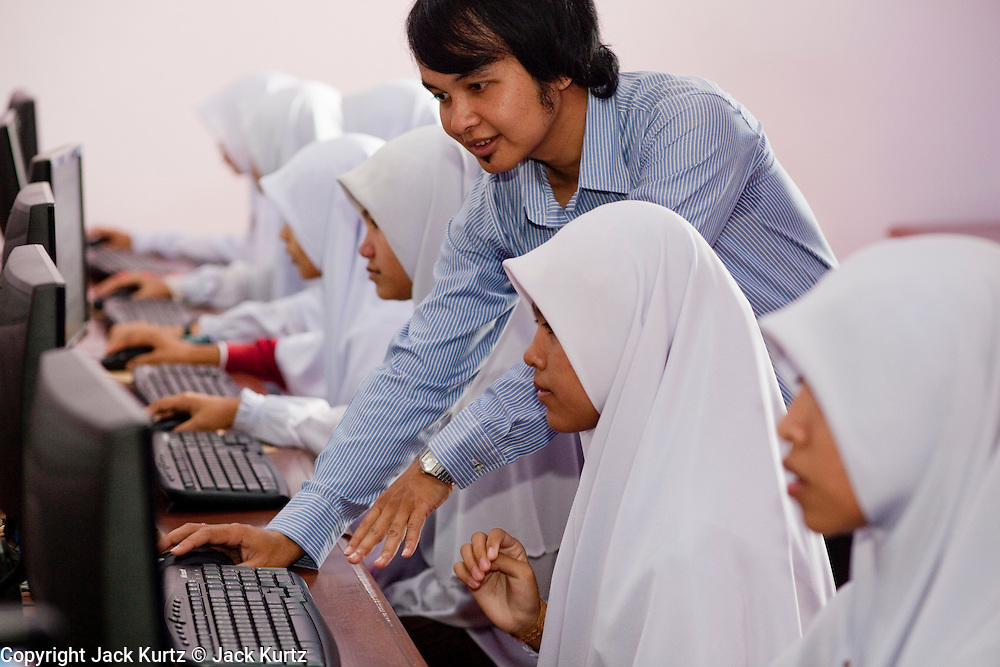"""Sept. 29, 2009 -- SAI BURI, THAILAND: A girl in a computer class at the Darunsat Wittya Islamic School in Sai Buri, Thailand. The school is the largest Muslim high school in Pattani province. Although it is a private school, the Thai government pays students' tuition to attend the school. The curriculum combines Thai official curriculum with Islamic curriculum. Many of the students go on to college level education in Egypt and Saudi Arabia. The Thai government views Islamic high schools with suspicion, fearing they radicalize students. Thailand's three southern most provinces; Yala, Pattani and Narathiwat are often called """"restive"""" and a decades long Muslim insurgency has gained traction recently. Nearly 4,000 people have been killed since 2004. The three southern provinces are under emergency control and there are more than 60,000 Thai military, police and paramilitary militia forces trying to keep the peace battling insurgents who favor car bombs and assassination.   Photo by Jack Kurtz"""