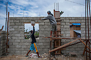 Mark Lorence M Bonife (R) aged 16, rebuilds his house in Palo village on June 13 2014 in Palo, Philippines. Tacloban city and the surrounding villages were devastated after typhoon Hayan passed over leaving at least 6,200 people dead and a high number of disappeared on November 8, 2013.