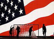 Workers prepare the stage in front of a giant television screen displaying a US flag 25 August 2004, at Madison Square Garden in New York City, site of the Republican National Convention. The convention begins 30 August, with US President George W. Bush expected to accept the nomination for president on 02 September.