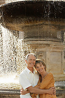 Middle-aged couple hugging by fountain Rome Italy portrait