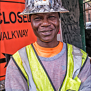 Smiling portrait of Emmanuel a West Africa American blue collar worker with yellow hard hat looking into the camera.