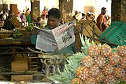 """Obst- und Gemüse-Verkäufer in der Markthalle von Havanna, Kuba, liest die offizielle kommunistische Tageszeitung """"Granma"""""""