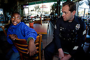 Sergeant Steve Muirhead talks with Tariq Al-Uqdah in a cafe on Thursday, Feb. 3, 2011 in South Central Los Angeles, Calif. Sergeant Muirhead frequently talks with children in the belief that the future of the community lies in the youth. (photo by Gabriel Romero ©2011)