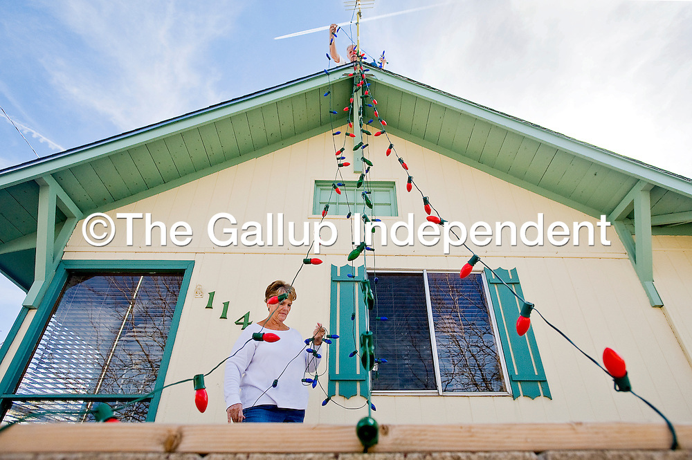 """110312       Cable Hoover<br /> <br /> Eva McFarland and her husband Perry McFarland, top, string Christmas lights on their home in Gallup Saturday. """"He gets a little carried away with it every year,"""" Eva said of the decorations """"but we've even won some certificates for it before."""""""
