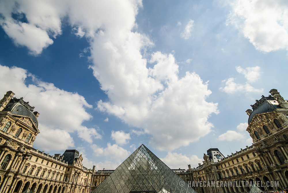 The Louvre museum in Paris, with the famous glass pyramid in the center at bottom of frame and puffy clouds overhead with copyspace.