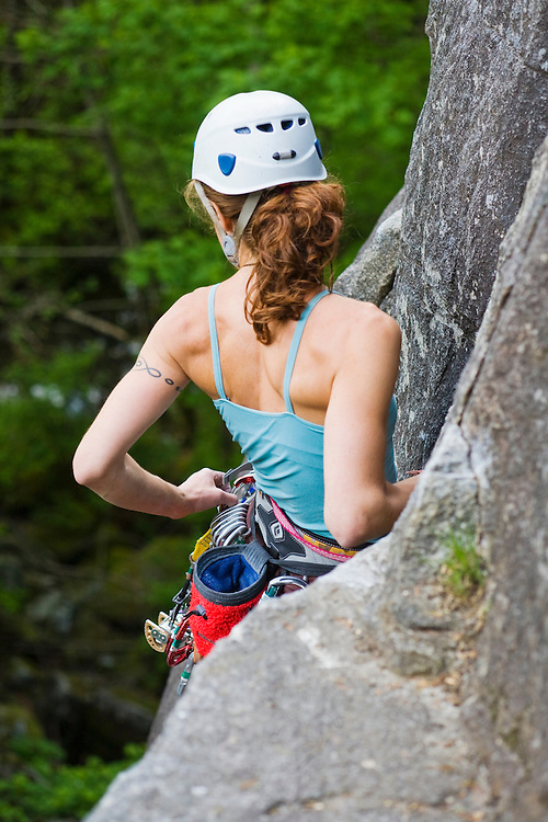 A young woman rock climbing at the Index, lower town wall, Index, Washington, United States