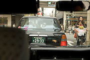 mother with child cycling through the narrow streets of Kyoto seen from inside a car