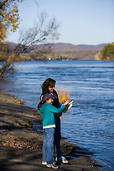 A mom and her daughter birdwatching on the banks of the Connecticut River in Holyoke, Massachusetts.  The Trustees of Reservations' Dinosaur Footprints preserve.