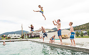 Two dads throwing kids into the pool, family fun at Durfee Hot Springs in Almo, Idaho near Castle Rock State Park and the City of Rocks National Reserve. MR