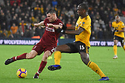 Wolverhampton Wanderers defender Willy Boly tackles Liverpool midfielder James Milner during the Premier League match between Wolverhampton Wanderers and Liverpool at Molineux, Wolverhampton, England on 21 December 2018.