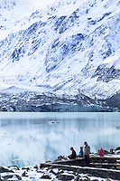 A mother and her two sons enjoy a picnic beside a glacial lake at the foot of Mt Cook at the head of the Hooker Valley Trail in Mt Cook National Park on the South Island of New Zealand.