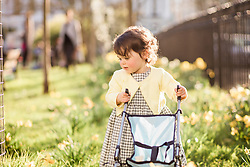Young Girl Pushing Toy Stroller in Park