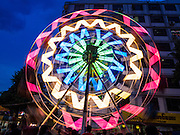 29 OCTOBER 2015 - YANGON, MYANMAR: A Ferris Wheel spins during a street carnival in central Yangon. Electricity is scarce in Myanmar, especially in rural areas, and most traveling carnivals use human powered rides. Workers climb to the top of the Ferris Wheel and then pull it around getting it spinning. They do the same with Merry Go Rounds, but instead of climbing to the top they pull it around. The carnival coincided with the Thadingyut Festival, the Lighting Festival of Myanmar, which is held on the full moon day of the Burmese Lunar month of Thadingyut, October or November on the Gregorian calendar. The carnival featured food, rides and games.      PHOTO BY JACK KURTZ
