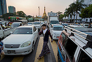 A man crosses a road during rush hour in downtown Yangon, Myanmar on December 14, 2015. (Photo by Kuni Takahashi)