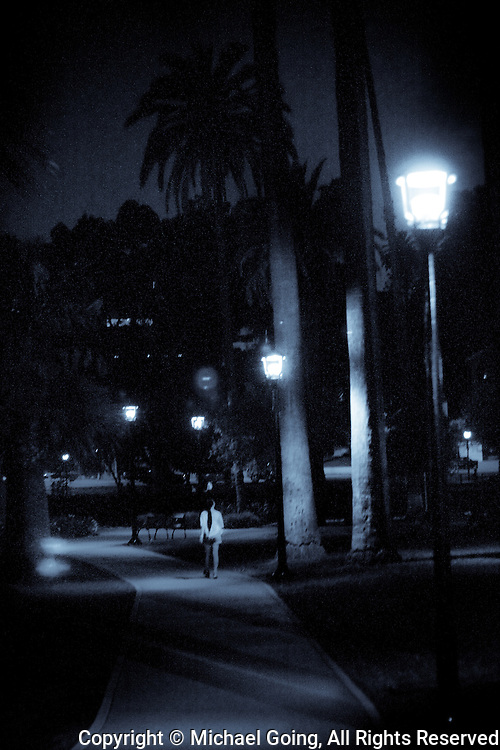 Woman walking on pathway at night with added noise and film grain filter