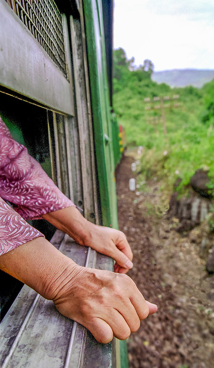 A woman rests her hands on the window sill of a train on the way to Hué in central Vietnam, 2003.